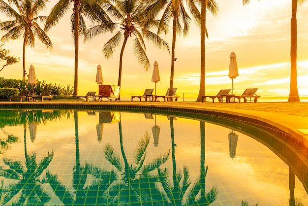 Umbrella and chair around swimming pool in hotel resort with sunrise in morning. holiday and vacation concept