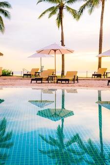 Umbrella and chair around swimming pool in hotel resort with sunrise in morning