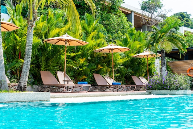 Umbrella and chair around swimming pool in hotel and resort