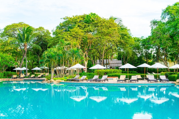 Umbrella and chair around swimming pool in resort hotel for leisure travel and vacation neary sea ocean beach at sunset or sunrise time