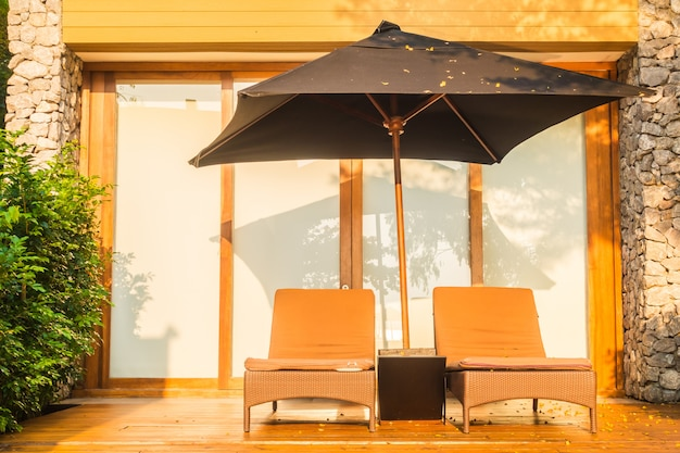 Umbrella and chair around swimming pool