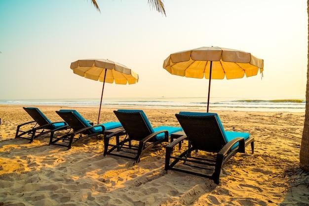 ヤシの木と日の出の海のビーチと傘の椅子のビーチ-休暇と休日のコンセプト