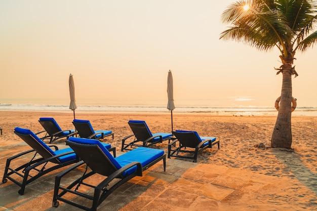 Пляж с зонтиком и шезлонгами с пальмами и морским пляжем во время восхода солнца. отпуск концепция праздника