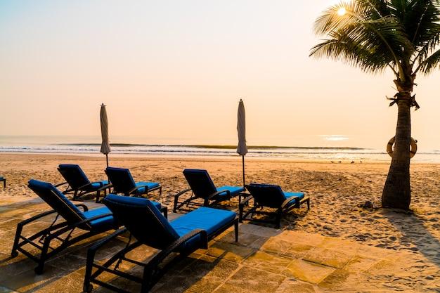 日の出時にヤシの木と海のビーチと傘椅子ビーチ