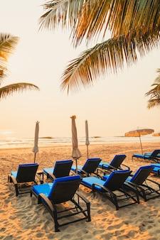 Пляж с зонтиком, пальмой и морем, пляж во время восхода солнца