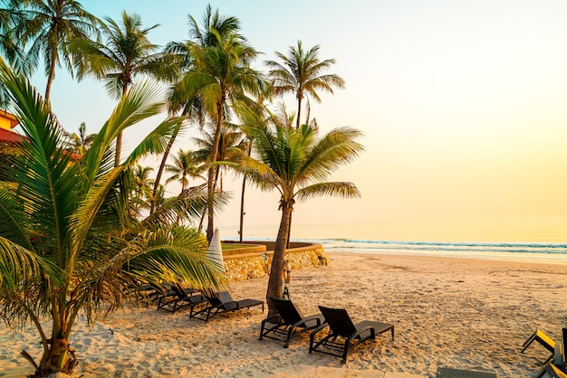 Umbrella and chair at beach with palm tree at sunrise
