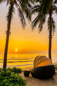 Umbrella and chair on the beautiful beach and sea at sunrise time for travel and vacation