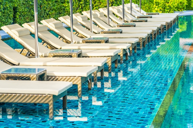 Umbrella and chair sofa around outdoor swimming pool in hotel resort for holiday vacation