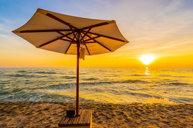 Umbrella and chair with pillow around beautiful landscape of beach and sea