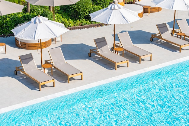 Umbrella and deck chair around outdoor swimming pool in hotel resort nearly sea beach ocean