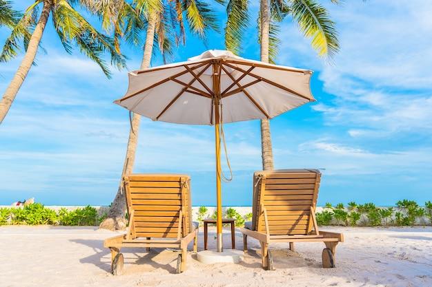 Ombrellone e sdraio intorno alla piscina all'aperto nel resort dell'hotel con spiaggia sull'oceano e palme da cocco