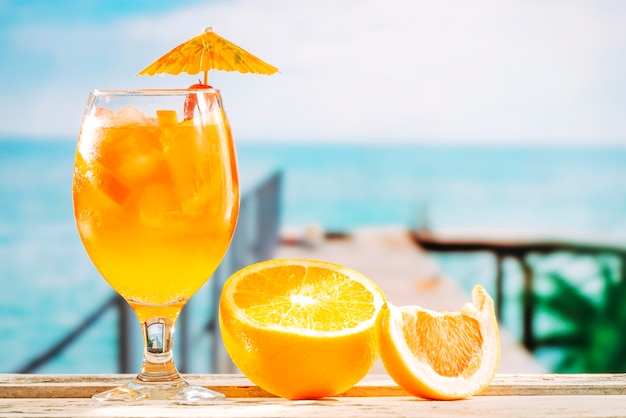 Umbrella decorated glass with orange drink and sliced orange on table
