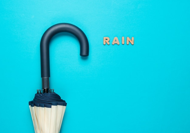 Umbrella hook with the word rain from wooden letters on blue surface.