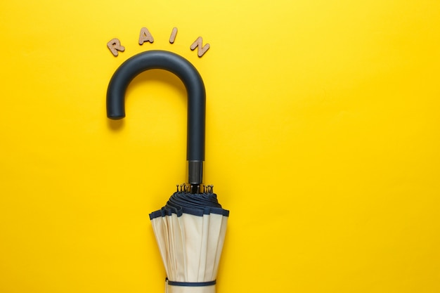 Umbrella hook with the word rain from wooden letters on a yellow surface.