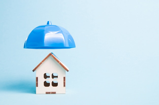 Umbrella over house, real estate insurance concept