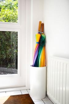 ドアの隣の明るい家の白い廊下のモダンなデザインで着色されたホルダー虹の傘