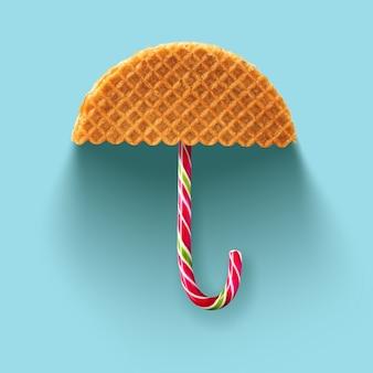 파란색 배경에 와플과 크리스마스 사탕으로 만든 우산.