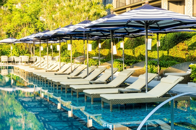 Umbrella and pool bed around outdoor swimming pool in hotel resort for holiday vacation