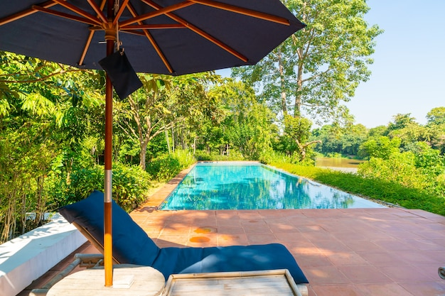 Umbrella and pool bed around swimming pool with river view