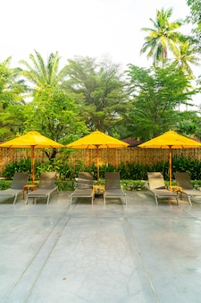 Umbrella and pool bed decoration around swimming pool in hotel resort