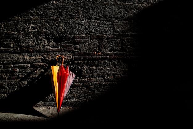 Заброшенный зонтик стоит у стены в солнечный день.