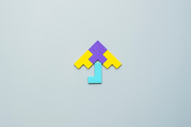 Umbrella shape block of colorful wood puzzle piece on gray .