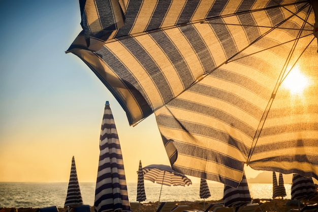 Umbrella and sun in front at sunset