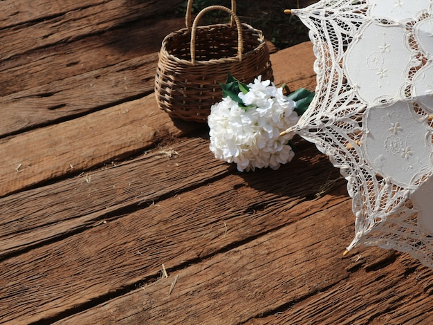 우산, 흰색 가짜 수국 꽃 꽃다발과 나무 바닥에 고리 버들 등나무 바구니