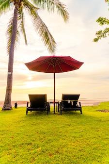 Зонтик со стулом на фоне морского пляжа и восхода солнца утром - концепция отпуска и праздника