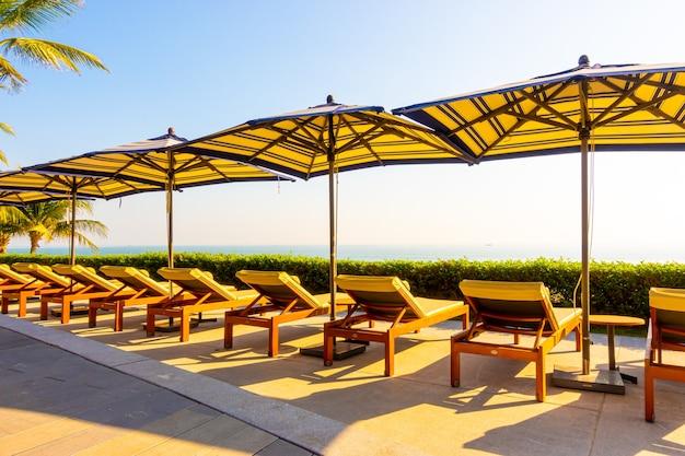 야외 수영장 주변의 우산과 의자