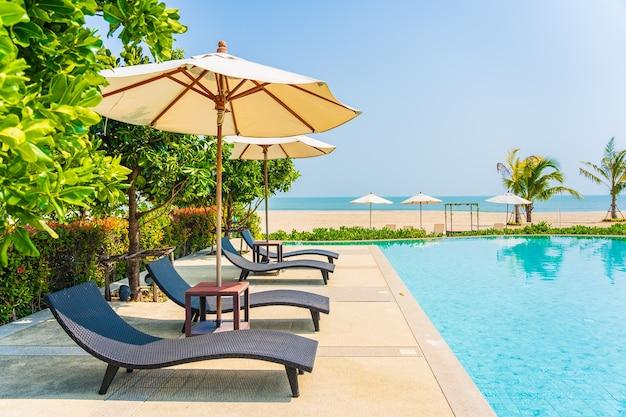야외 수영장 주변의 우산과 야외용 데크 의자