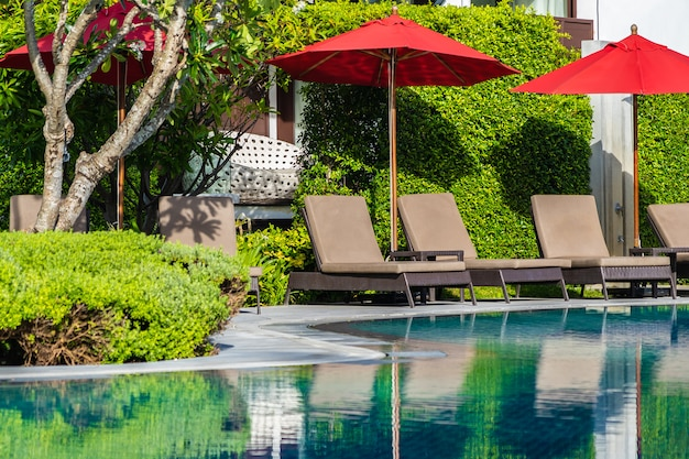 Umbrellas and deck chairs around outdoor swimming pool