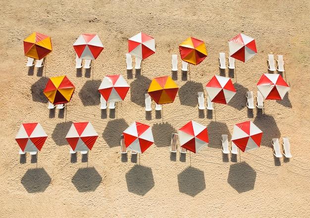 Зонтики с пустыми шезлонгами утром на песке морского пляжа