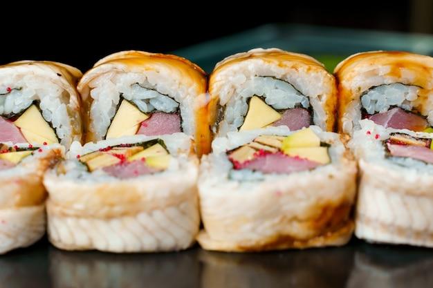 우나기는 참치, 토비코 캐비어, 체다 치즈, 노리, 우나기 소스 클로즈업으로 롤링합니다. 일본 전통 음식.