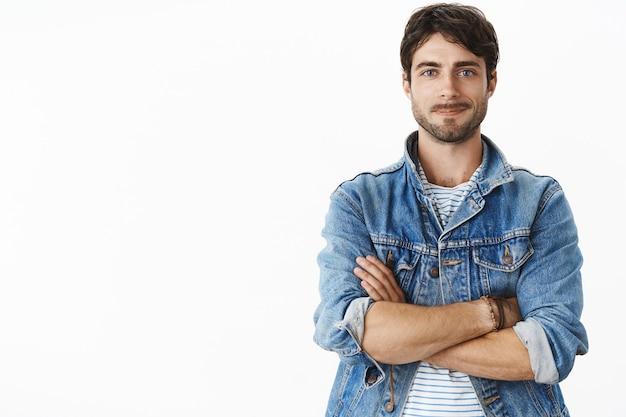 Colpo inalterato di carismatico bell'uomo adulto caldo con barba e occhi azzurri in elegante giacca di jeans su t-shirt a righe sorridente ottimista, gioioso come in piedi in posa sicura con le mani incrociate
