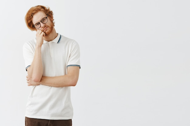 Неуравновешенный бородатый рыжий парень позирует у белой стены в очках