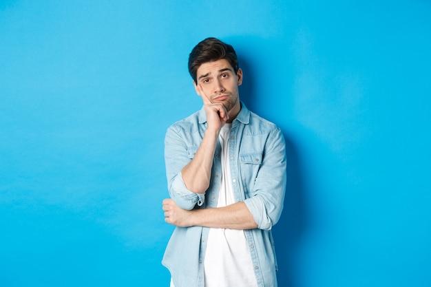Uomo distratto e annoiato che guarda senza interesse la telecamera, in piedi su sfondo blu