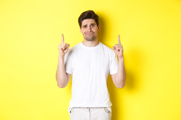 Unamused handsome guy frowning, pointing fingers up at something bad, standing skeptical against yellow background.