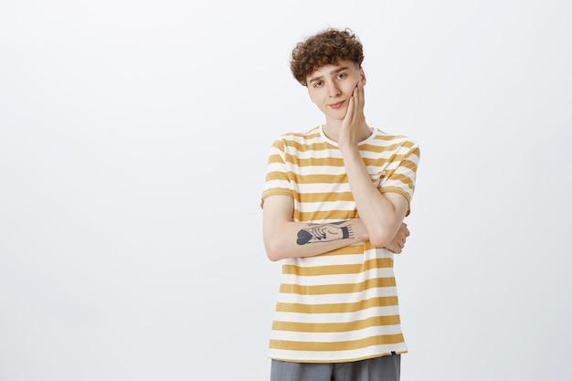 Ragazzo adolescente non divertito e riluttante in posa contro il muro bianco