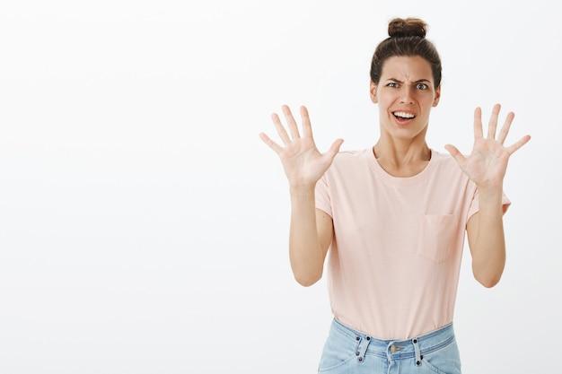 Giovane donna alla moda disinteressata e riluttante che posa contro il muro bianco