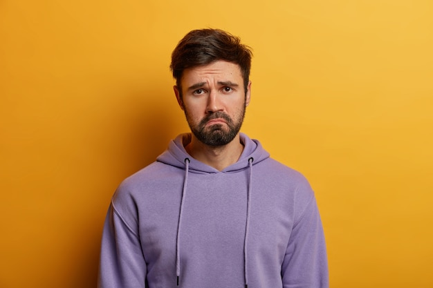 Unamused sad miserable guy purses lips, frowns face with dissatisfaction, wears hoodie, poses indoor against yellow wall, sulks troubled as someone hurt his feelings, wears purple hoodie