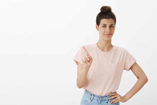Unamused young stylish woman posing against the white wall