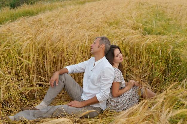 밀밭에 잔디에 앉아 불행한 사랑 커플. 남자와 여자가 싸웠다.