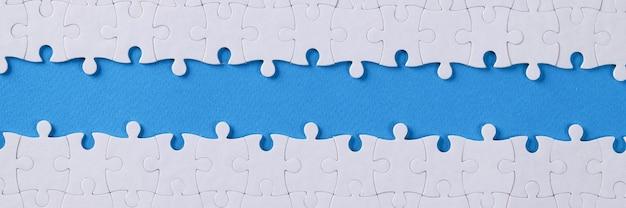 Белая головоломка в разобранном виде посередине на фоне голубя
