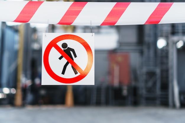 許可なく立ち入ることは禁止されています。ポスターは、植物への通路を保護する赤と白のリボンに掛けられています。