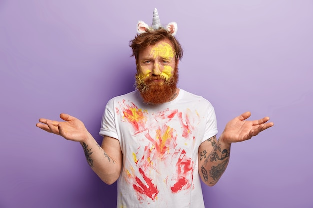 カラフルな水彩画で汚れた、気づいていないひげを生やした若い男、優柔不断な表情で手を広げ、ユニコーンの角と耳を身に着け、斑点のある白いtシャツを着て、紫色の壁に隔離されています