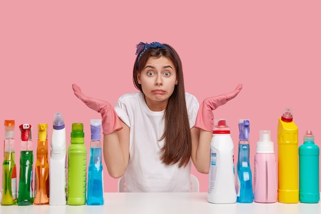 Unaware cleaning girl wears pink rubber protective gloves, spreads hands with hesitation, poses at white desk with cleaning detergents, cant decide which room tidy up first. housework concept