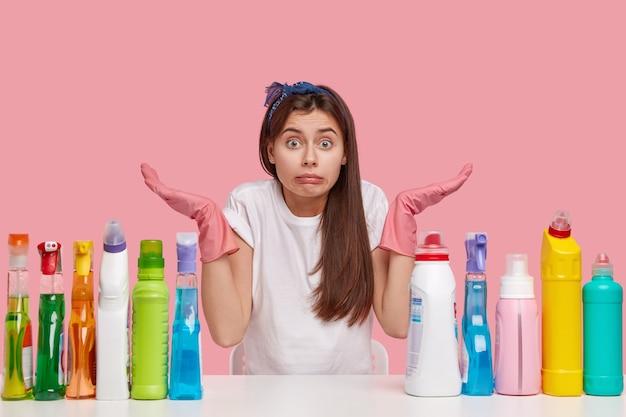 Ignara ragazza delle pulizie indossa guanti protettivi di gomma rosa, allarga le mani con esitazione, posa alla scrivania bianca con detergenti per la pulizia, non può decidere quale stanza riordinare per prima. concetto di lavori domestici