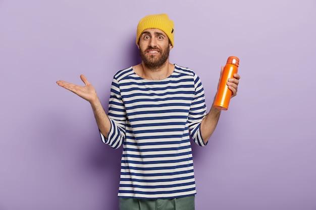 Ignaro confuso uomo caucasico alza il palmo con esitazione, tiene la fiaschetta arancione con una bevanda calda, indossa un cappello giallo e un maglione a strisce