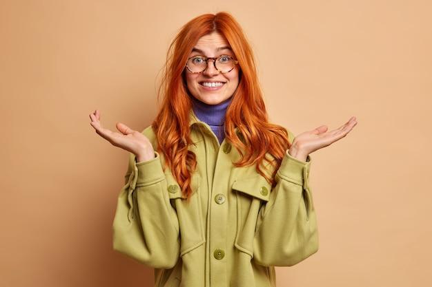 生姜髪の元気な若いヨーロッパ人女性が気づかずに手のひらを上げると、疑わしい表情ですぐに答えられない緑色のジャケットを着ています。